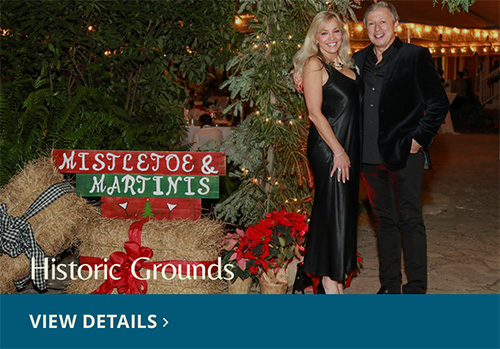 Couple standing in front of Mistletoe and Martini holiday party sign. View Details