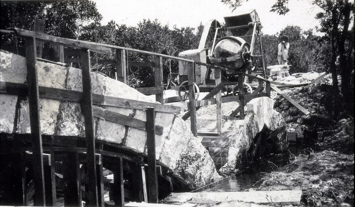 Worker posing with concrete mixer during construction of the Chinese Bridge in 1916 on today's 72 Avenue