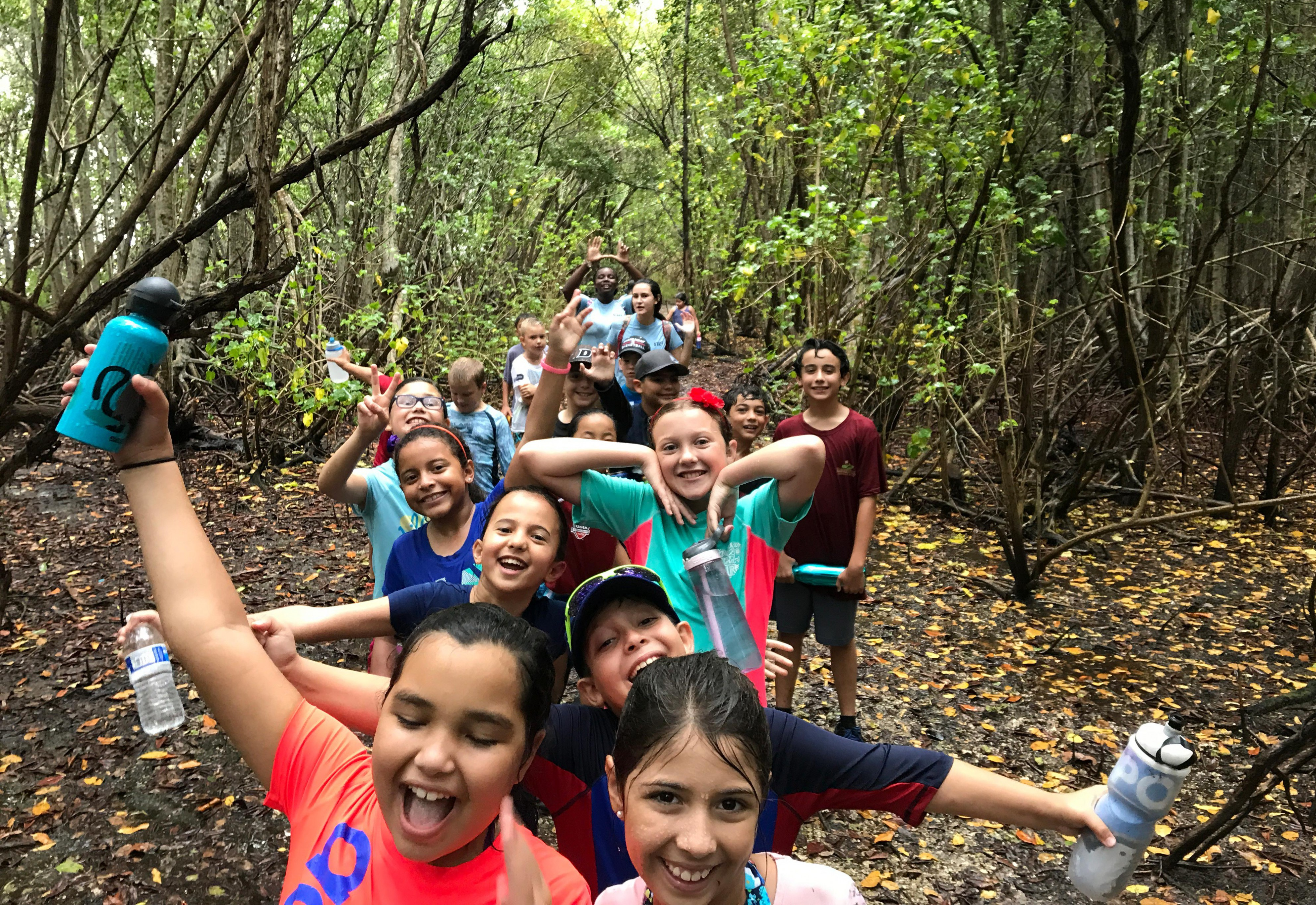 summer campers on a hike in the rain through the natural areas of the park