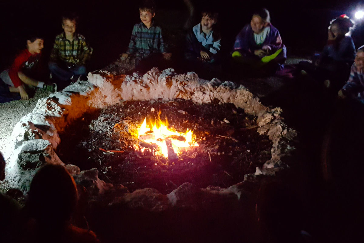 Group of campers gathered around the campfire after a night hike at Deering Estate