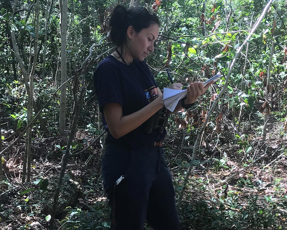 Intern writing notes during a field study