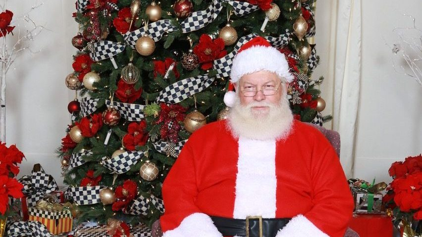 Santa Claus sitting in front of a decorated christmas tree surrounded by presents in the ball room of the stone house