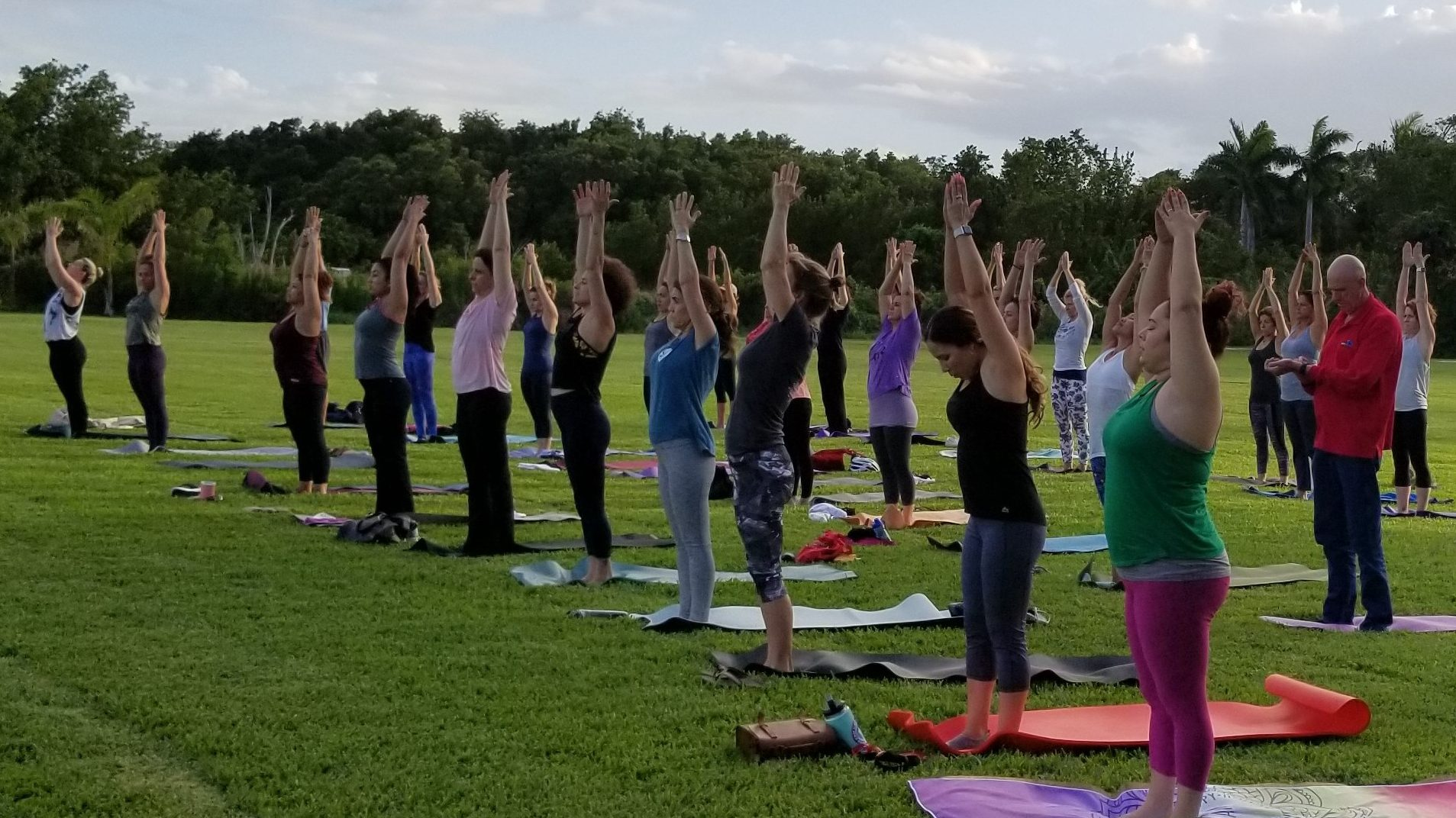 Large group gathered on the main lawn of Deering Estate for Full Moon Yoga