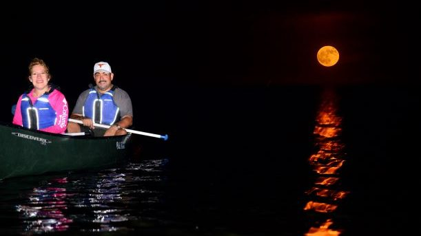 Couple tandem kayaking on the open water with the full moon as their background during Deering's moonlight kayak tour