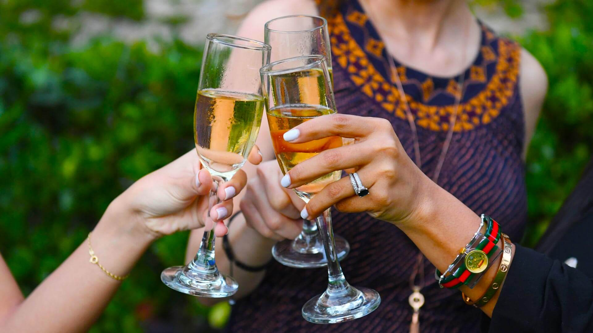 guests toasting glasses of champagne at a celebration in the courtyard