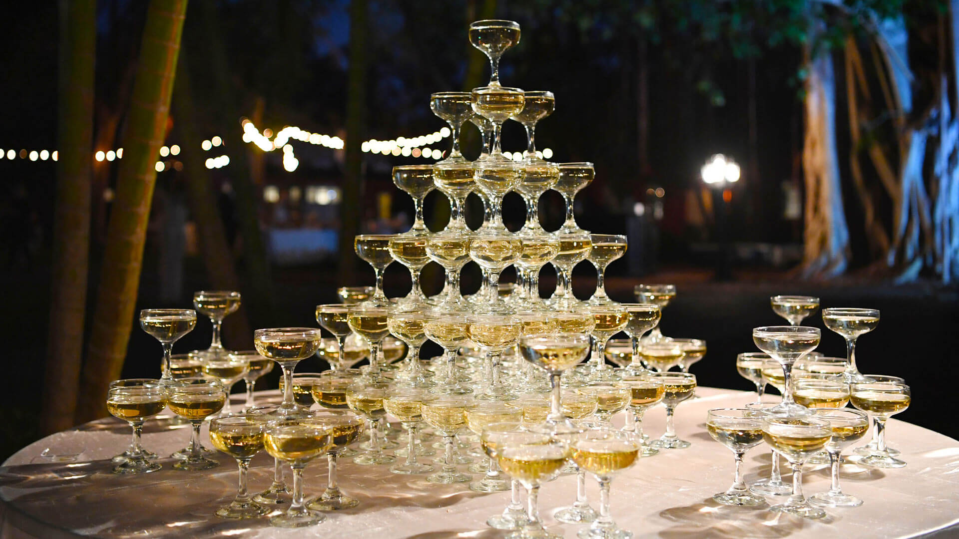 a tower of champagne classes on a table during a wedding or celebration