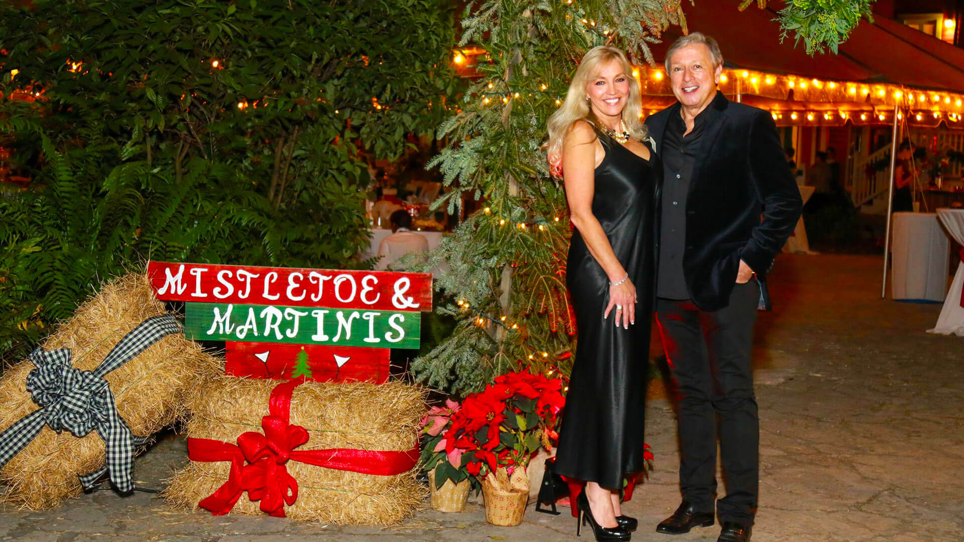 Couple standing in front of Mistletoe and Martini holiday party sign