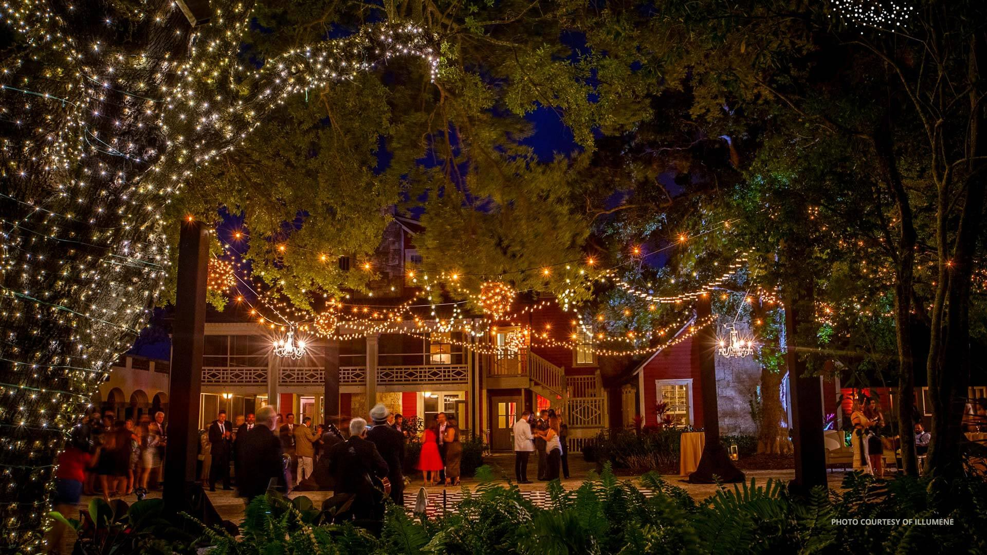the courtyard lit up at night with custom lighting for a wedding celebration