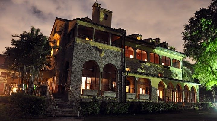 Deering Estate's Stone House dimly lit up at night in preparation for their Ghost Tour