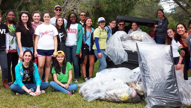 Group of young volunteers gathered together with all of the trash they cleaned up