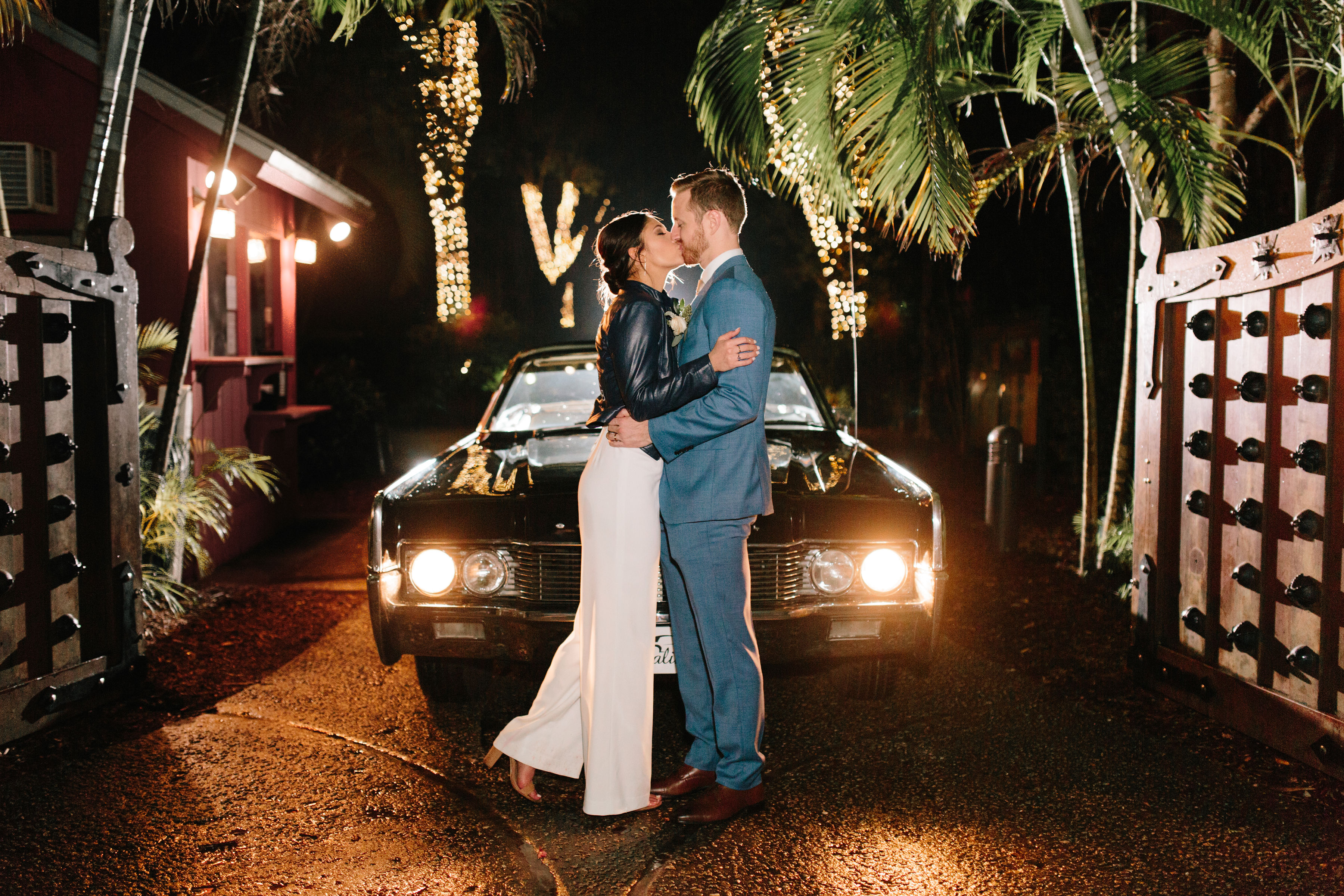 a newly married couple kissing for photo in front a car at the entrance to the estate