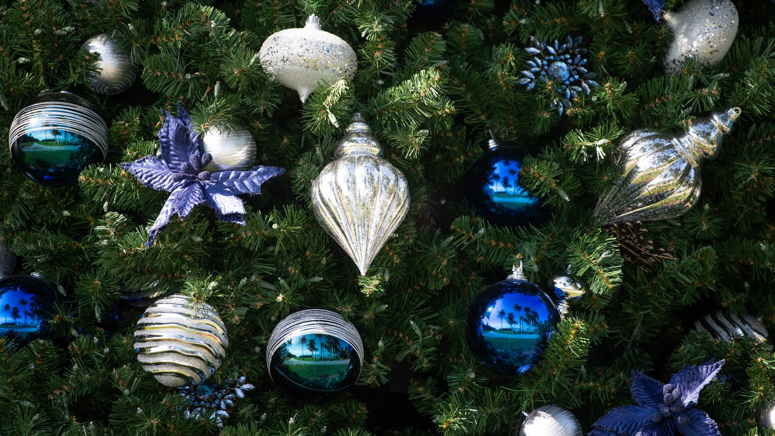 small festive ornaments covering a Christmas tree