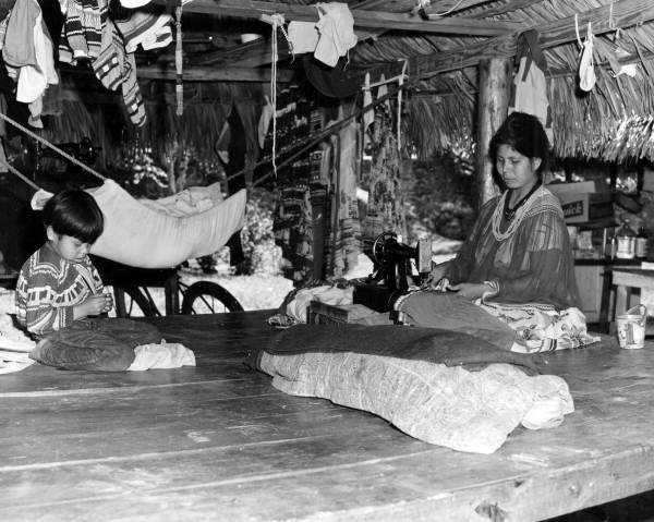 June 1950, Seminole woman with child. Woman is seen sewing in her chickee at the Musa Isle village in Miami, Fl. Florida Memory Project (State Archives of Florida)