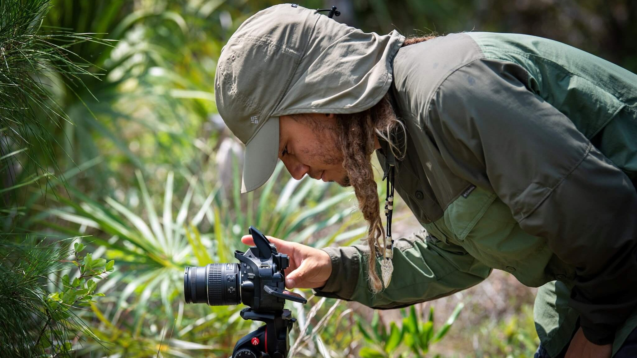 Photographer taking close-up pictures of Deering Estate's foliage.