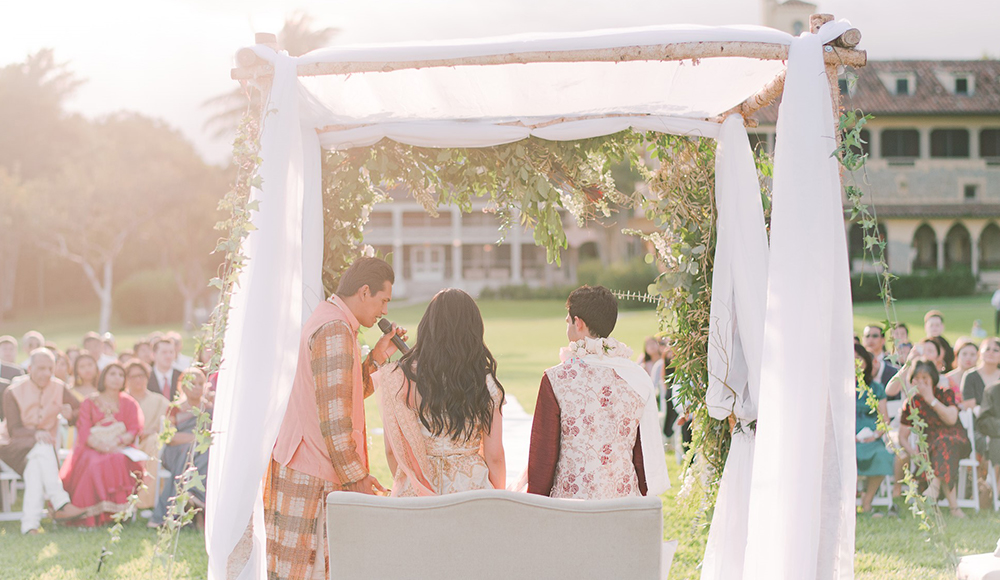 Intimate wedding ceremony taking place on Deering Estate's main lawn during sunset.