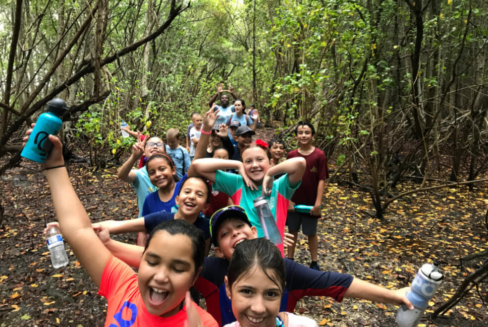 Kids on a hikes to learn about nature on a field trip in Miami.