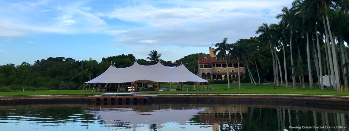 photo of a sailcloth tent at Deering Estate's Grand Waterfront Lawn. The tent's reflection and the Stone House Museum's reflection is visible in the water.