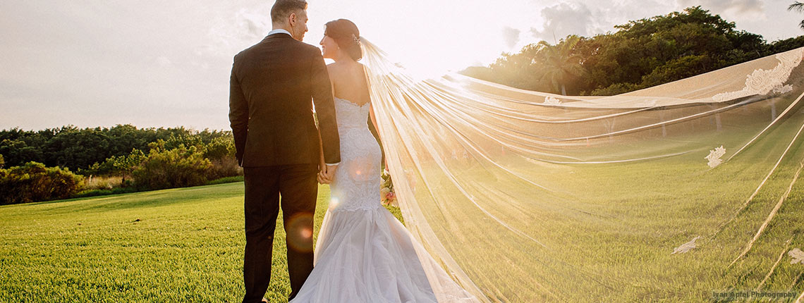 sunset photo of a couple at Deering Estate's Grand Waterfront Lawn. The couple is encompassed by a beautiful warm glow from the sun setting.