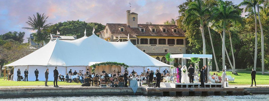 photo of an outdoor ceremony at Deering Estate's Grand Waterfront Lawn with a sailcloth reception tent behind the ceremony area. The Grand Waterfront Lawn's size can accommodate ceremonies and receptions of many sizes.